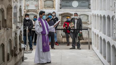 A priest conducts a ceremony after the funeral of Covid-19 victims at El Angel cemetery, in Lima on May 21.