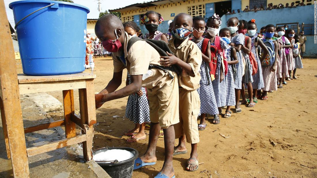 Preschool students wearing face masks wait to wash their hands at a makeshift sink before class in Abidjan, Côte d'Ivoire, on Monday, May 25. The country became one of the first in West Africa to restart lessons after a two-month coronavirus shutdown.