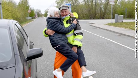 Inga Rasmussen, left, from Denmark is lifted up by Karsten Tüchsen Hansen from North Frisia, Germany, during their daily meeting at the German-Danish border on April 24.