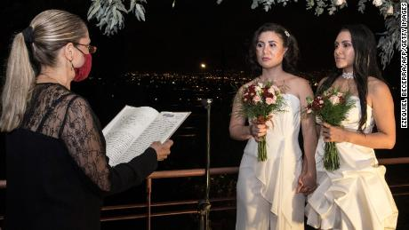 Alexandra Quiros (center) and Dunia Araya (right) stand before a lawyer during their wedding in Heredia.