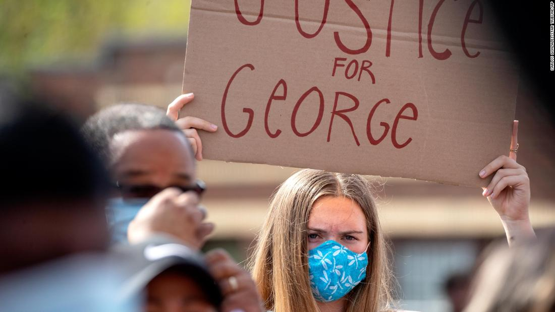 "A demonstrator holds a sign reading ""Justice for George"" at Chicago Avenue and East 38th Street in South Minneapolis."