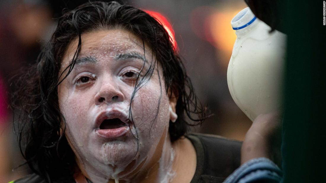 Milk is poured on the face of a protester who had been exposed to percussion grenades and tear gas Tuesday in Minneapolis.