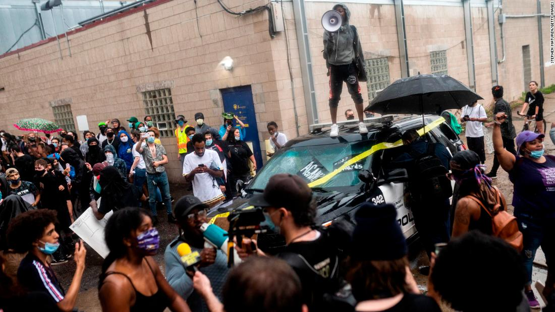 Protesters rally around a damaged police vehicle in Minneapolis.