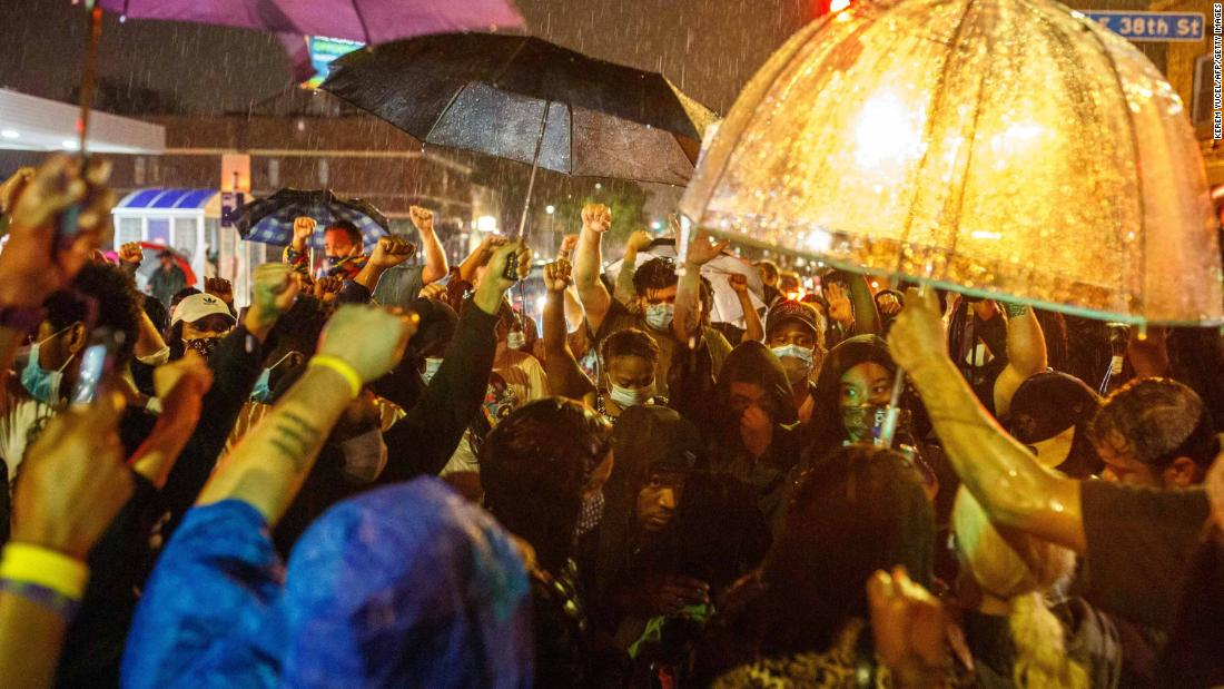 Protesters gather in the rain Tuesday in Minneapolis near the spot where Floyd was arrested.
