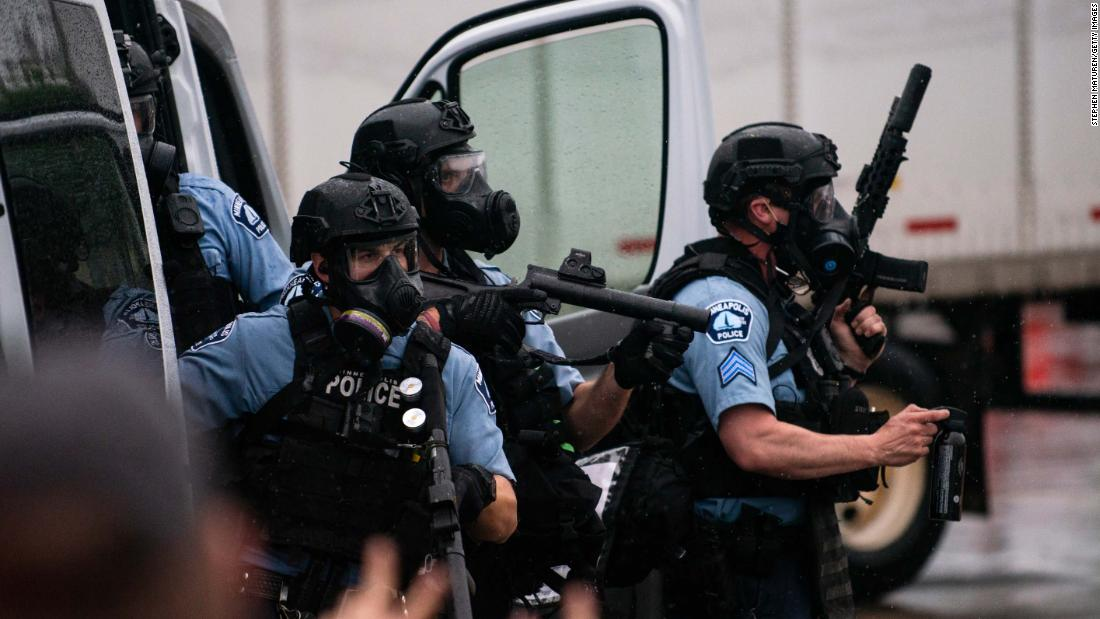Police dressed in tactical gear attempt to disperse crowds in Minneapolis.