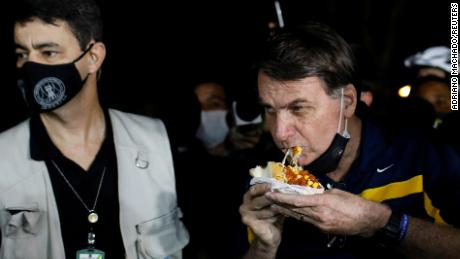 Bolsonaro was met with angry protestors when eating a hotdog in Brasilia.