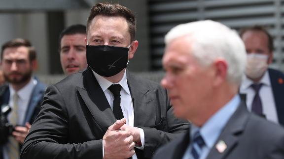 """SpaceX founder <a href=""""https://www.cnn.com/2020/05/13/us/gallery/elon-musk/index.html"""" target=""""_blank"""">Elon Musk</a> wears a face mask while standing near Vice President Mike Pence."""