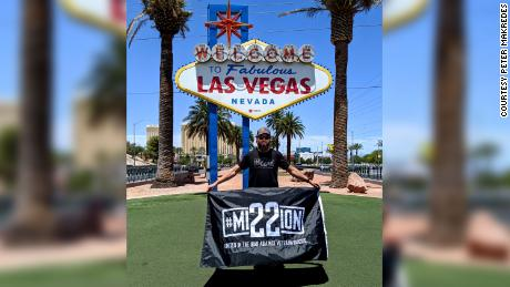 Peter Makredes holds a Mission 22 banner in Las Vegas.