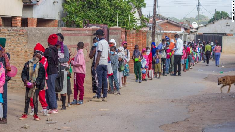 Children queue for food outside Murozoki's kitchen in Zimbabwe.
