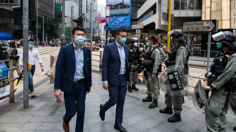 People walk past riot police on May 28, 2020 in Hong Kong, China.