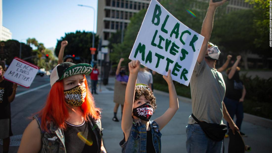 Kika Villareal, left, and her daughter Aubrie march with fellow Black Lives Matters protesters on Wednesday in Los Angeles.