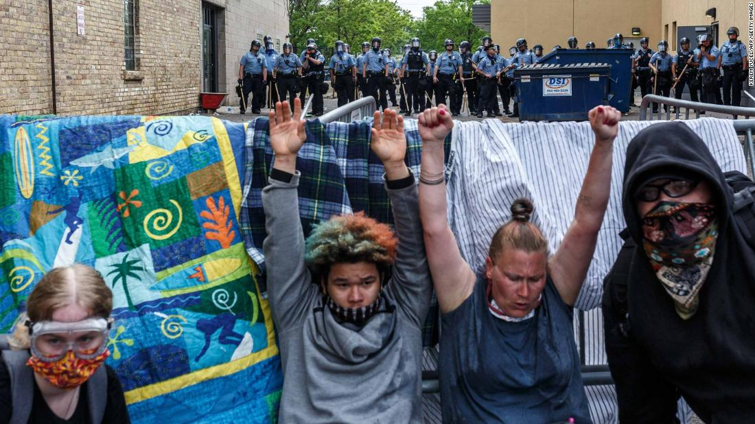 Protesters raise their hands up as they react to tear gas during a demonstration in Minneapolis on Wednesday.
