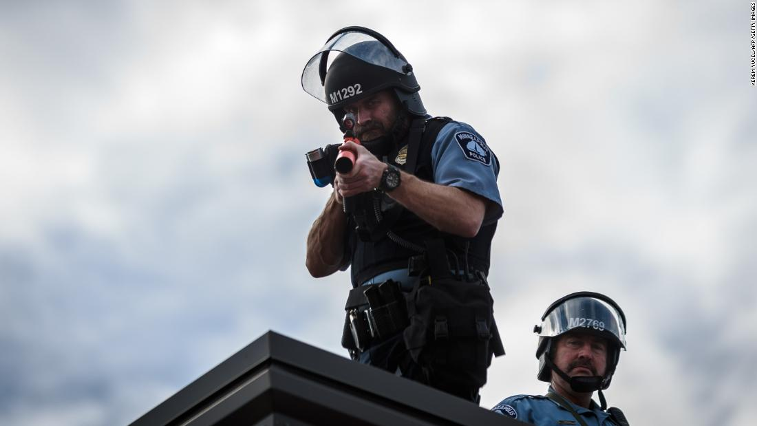 Two police officers stand on the roof of the Third Precinct holding a projectile launcher during Wednesday's demonstration in Minneapolis.