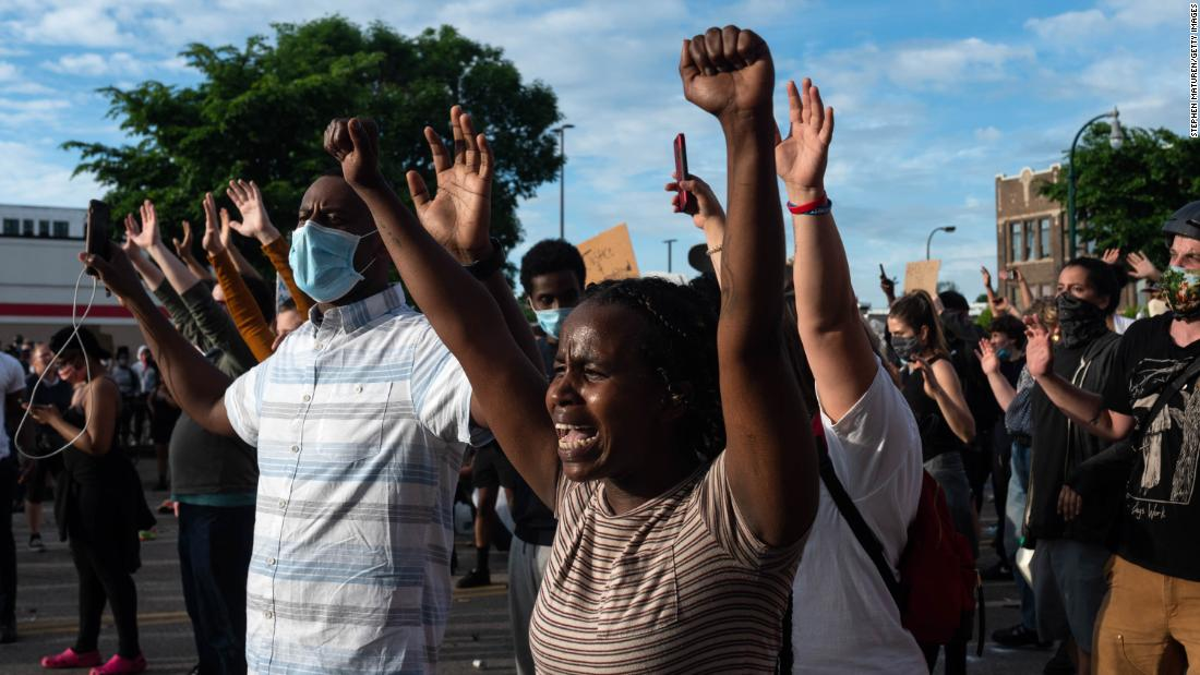 Demonstrators in Minneapolis raise their hands Wednesday as they standoff with police.