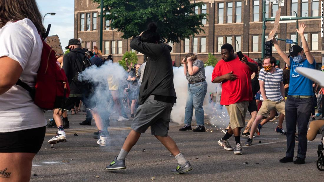Minneapolis protesters react Wednesday as a projectile launched by police explodes near.
