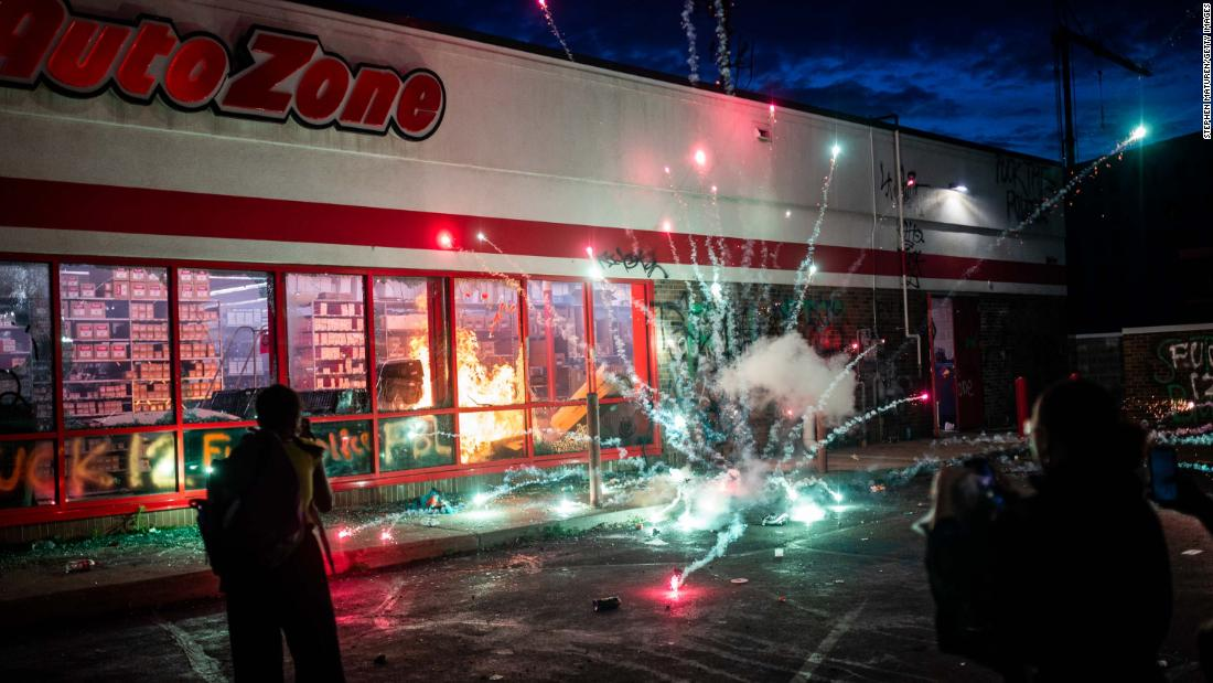 A firework explodes as a fire burns Wednesday inside an Auto Zone store near the Third Precinct in Minneapolis.