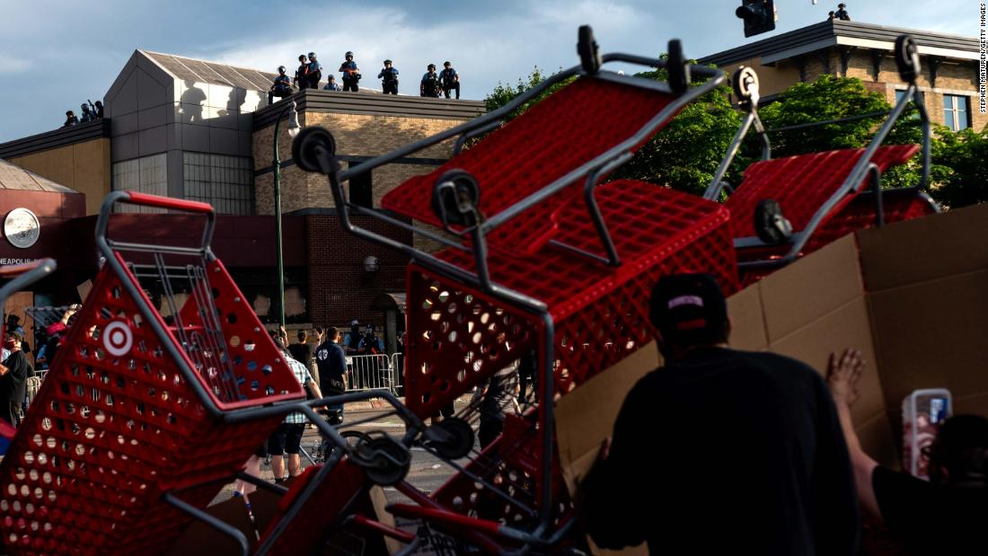 Protesters use shopping carts as a barricade as they confront police near the Minneapolis Police Third Precinct on Wednesday.