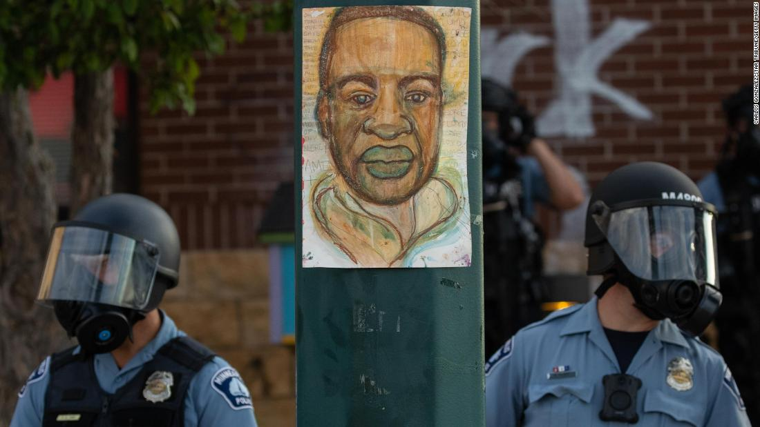 Minneapolis police stand by an illustration of Floyd as demonstrators rally on Wednesday.