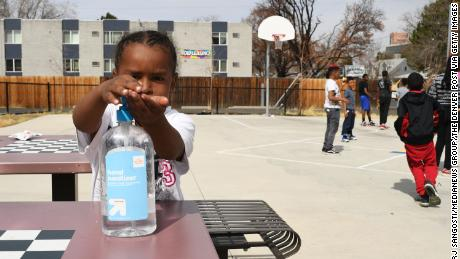 Messiah Guyton, 4, puts on hand sanitizer before eating his snack in Aurora, Colorado.