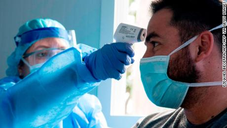 A health worker checks the temperature of a man at a clinic in San Jose, on May 18, 2020, amid COVID-19 pandemic measures.