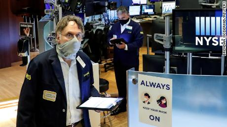 Traders wearing masks work, on the first day of in person trading since the closure during the outbreak of the coronavirus disease on the floor at the New York Stock Exchange.