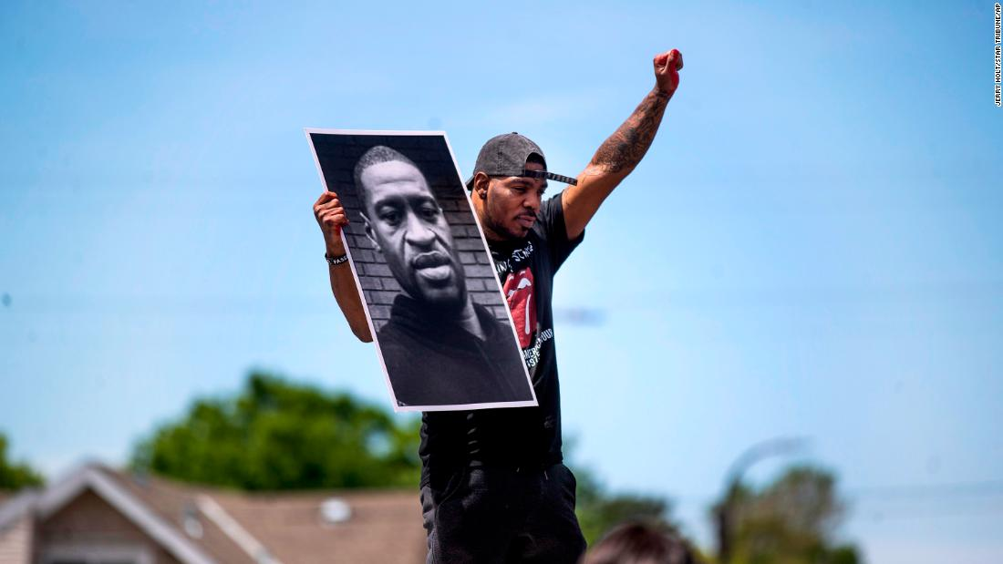 Tony L. Clark holds up a poster of Floyd on Thursday near Cup Foods in Minneapolis.