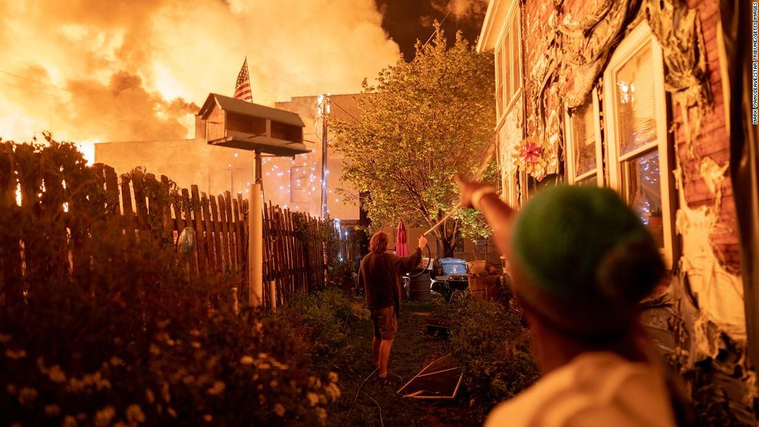 Neighbors fight with garden hoses and buckets to save homes after rioters set fire to a multi-story affordable housing complex under construction near the Third Precinct on Wednesday, May 27, in Minneapolis.