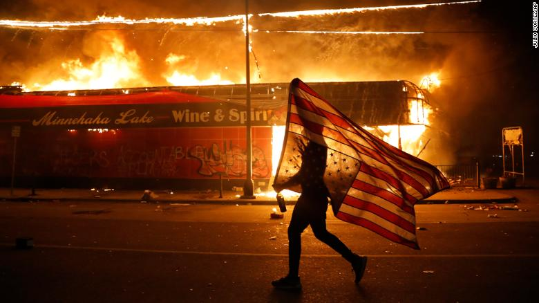 A protester carries the US flag next to a burning building in Minneapolis.