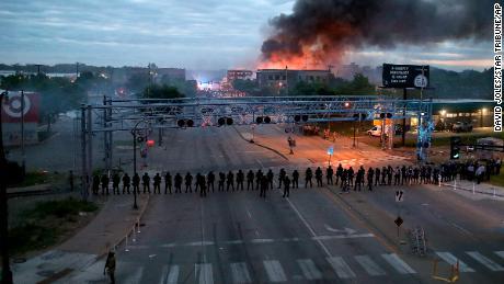 Offiziere bilden am Freitag eine Linie entlang der Lake Street in der Nähe der Hiawatha Avenue, während nach einer Nacht voller Unruhen und Proteste gegen den Tod von George Floyd in Minneapolis Feuer brennen.