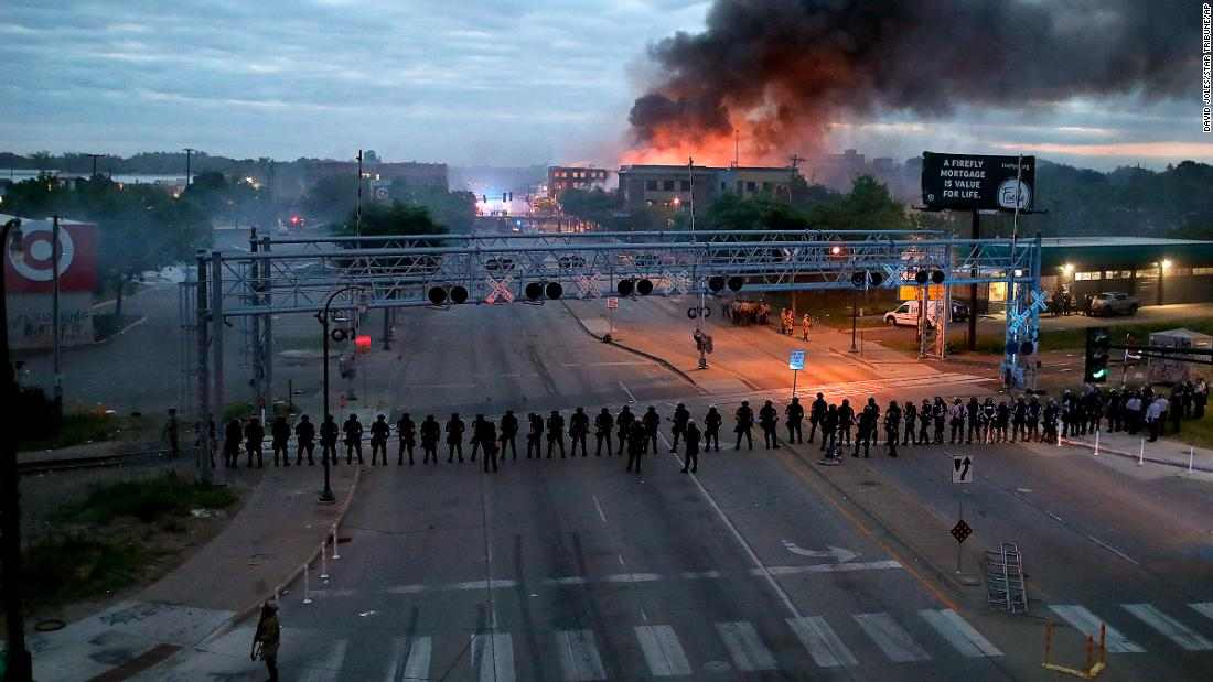 Law enforcement officers gathered along Lake Street early on Friday, as fires burned after a night of unrest in Minneapolis.
