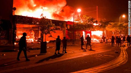 TOPSHOT - Flames rise from a liquor store and shops near the Third Police Precinct on May 28, 2020 in Minneapolis, Minnesota, during a protest over the death of George Floyd, an unarmed black man, who died after a police officer kneeled on his neck for several minutes. - A police precinct in Minnesota went up in flames late on May 28 in a third day of demonstrations as the so-called Twin Cities of Minneapolis and St. Paul seethed over the shocking police killing of a handcuffed black man. The precinct, which police had abandoned, burned after a group of protesters pushed through barriers around the building, breaking windows and chanting slogans. A much larger crowd demonstrated as the building went up in flames. (Photo by Kerem Yucel / AFP) (Photo by KEREM YUCEL/AFP via Getty Images)