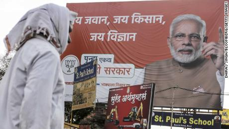 A pedestrian walks past a Bharatiya Janata Party (BJP) election campaign hoarding featuring India's Prime Minister Narendra Modi in Beed, Maharashtra, India, on Sunday, Apr. 14, 2019. A three-year drought has left some farmers with no income to pay back loans, with tragic consequences: Beed reportedly has the state's highest rate of farmer suicides. As many as 12,602 farmers and agricultural laborers in India committed suicide in 2015, according to the last available data before the government stopped releasing figures. Maharashtra, along with neighboring Telangana and Karnataka, accounted for half of the deaths among India's 29 states that year. Photographer: Dhiraj Singh/Bloomberg via Getty Images