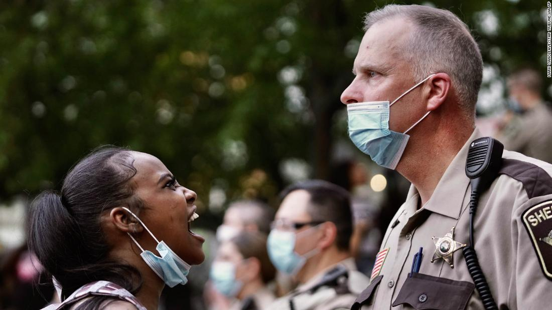 A woman yells at a sheriff's deputy during a protest Thursday in Minneapolis.