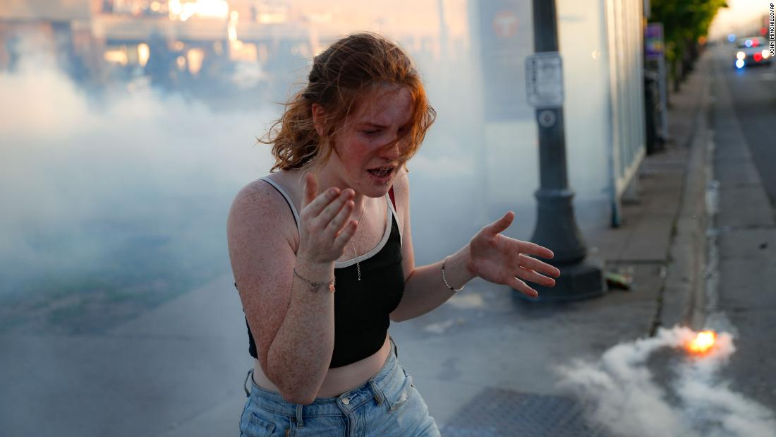 A protester reacts in the midst of a cloud of tear gas Thursday in St. Paul, Minnesota.