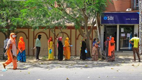 People wait outside a bank during lockdown in Jaipur, Rajasthan, India, on April 9.