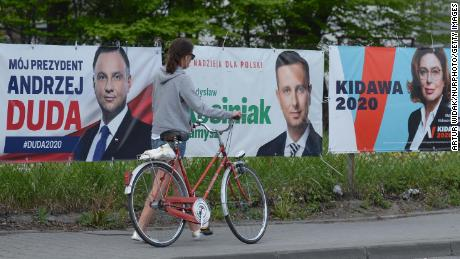 A lady walks by election banners with images of candidates (L-R) Andrzej Duda, Wladyslaw Kosciniak-Kamysz and Malgorzata Kidawa, seen outside Krakow. The Presidential Election is scheduled to be held in Poland on May 10, 2020. During the COVID-19 pandemic the government's plan of holding the election as originally scheduled during the pandemic has been heavily criticised. However, the Law and Justice ruling party (PIS) is still going ahead with the election in May through a postal vote. On Monday, May 4, 2020, Krakow, Poland. (Photo by Artur Widak/NurPhoto via Getty Images)