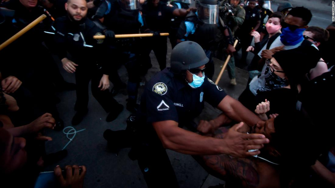 Police officers and protesters clash near the CNN Center in Atlanta on Friday.