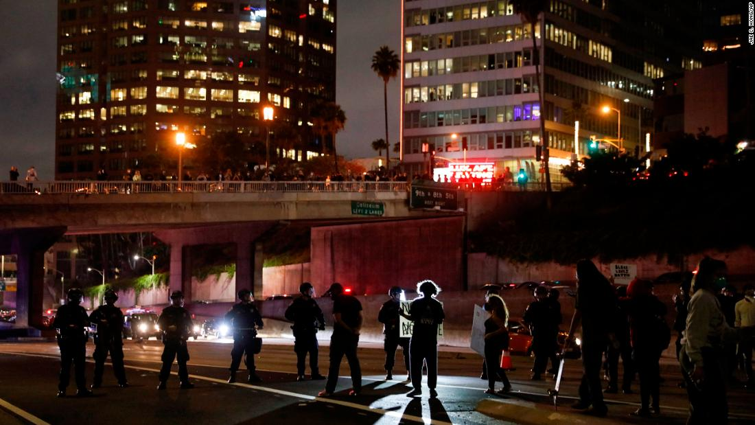 Protesters confront police officers while blocking the 110 Freeway in Los Angeles.