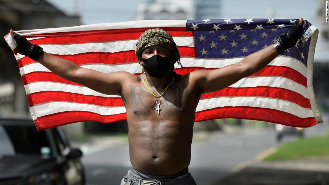 A protester holds up an American flag in New Orleans on Friday.