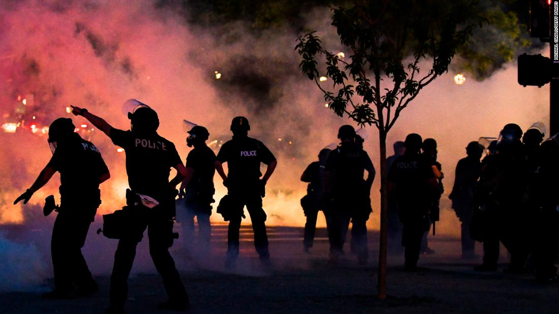 Police officers fire tear gas at protesters near the Colorado state Capitol in Denver on Friday.