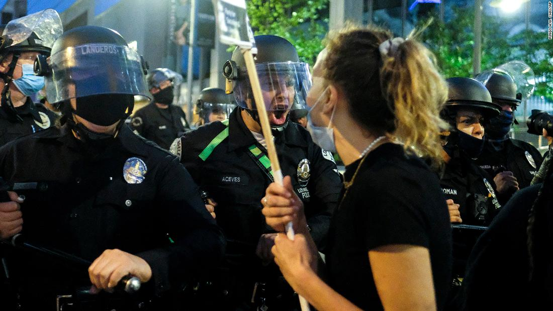 Police officers move forward to clear the street during a protest in downtown Los Angeles on Friday.