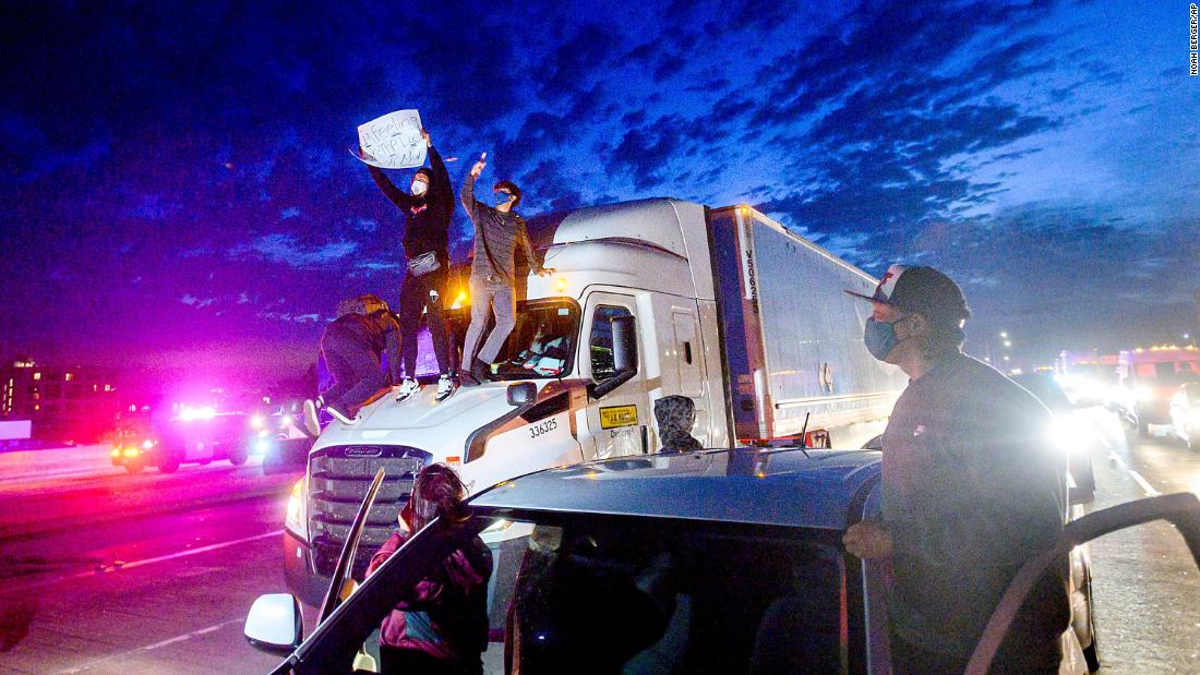 Demonstrators climb atop a truck while blocking all lanes of traffic on Interstate 880 in Oakland, California, on Friday.