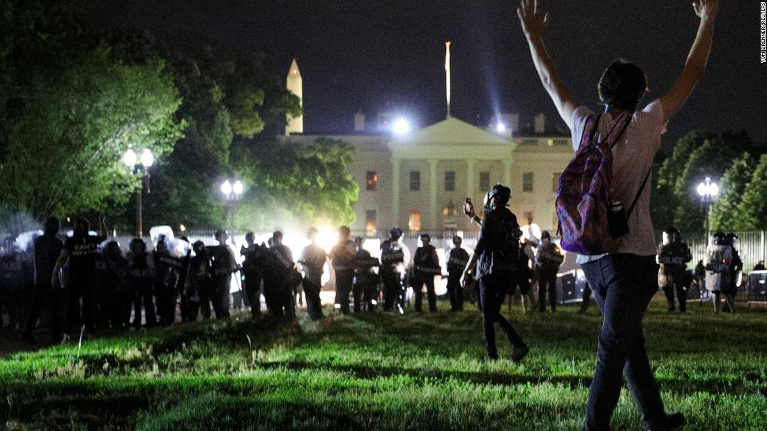 A protester holds his hands up as police officers keep demonstrators away from the White House in Washington early Saturday, May 30.