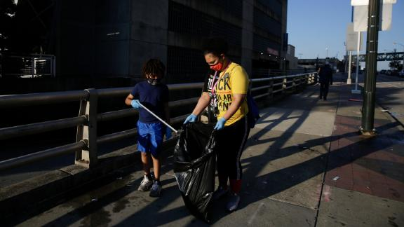 Derico Crump, 9, left, and Dayshell Crump, 30, clean the streets of downtown Atlanta in the aftermath of a demonstration against police violence on Saturday, May 30, 2020, in Atlanta. (AP Photo/Brynn Anderson)