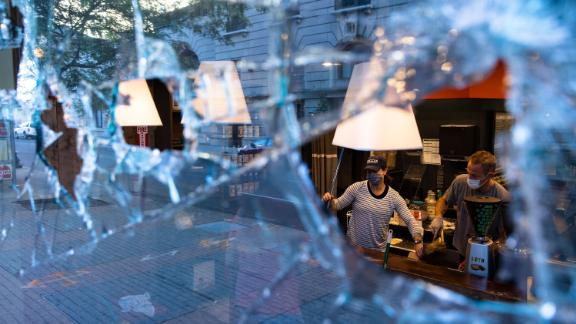Workers clean up damaged businesses Saturday after a night of protests in Louisville, Kentucky.