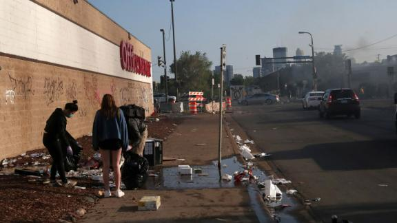 Community members clean up Saturday after another night of protests in Minneapolis.