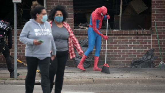 A person dressed as Spiderman sweeps the sidewalk as residents help clean up in Minneapolis.