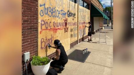 Emi Nijiya, left, and Amo Azure spray paint their tattoo parlor with slogans in support of protesters.
