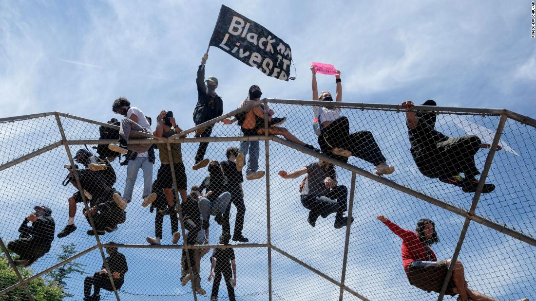 People stand on top of a baseball backstop during a protest in Los Angeles on Saturday, May 30.