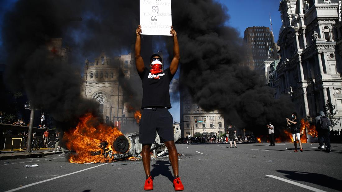 A protester holds a sign while a vehicle burns in the street in Philadelphia on Saturday.